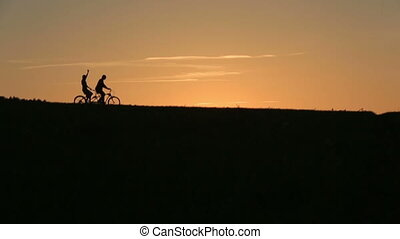 Silhouette of  Beautiful Couple Slowly Riding The Tandem Bicycles While Sunset. Summer Nature Background with Beautiful Clouds in the Sky Close Up.