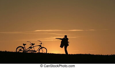 Silhouette of Beautiful Couple With Tandem Bicycles. -...