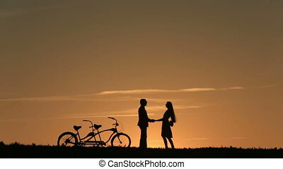 Silhouette of Beautiful Couple With Tandem Bicycles Watching...