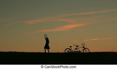 Silhouette of Beautiful Couple With Tandem Bicycle. Girl...