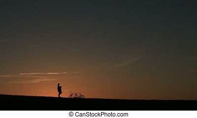 Silhouette of Beautiful Couple With Tandem Bicycle . Man...