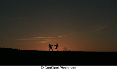 Silhouette of Beautiful Couple With Tandem Bicycle Walking...