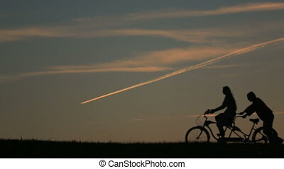 Silhouette of Beautiful Couple With Tandem Bicycles. Girl...