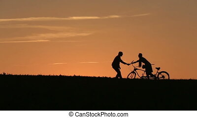 Silhouette of Beautiful Couple With Tandem Bicycles Play The...