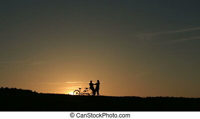 Silhouette of  Beautiful Couple With Tandem Bicycles Dancing Holding Hands Against Fabulous Sunset Backgrund .