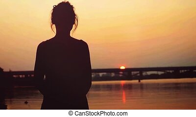 Silhouette of beautiful woman standing on sandy beach, watching sun going down in slowmotion, during sunset.