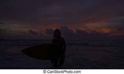 Silhouette of beautiful woman with surfboard during amazing sunset