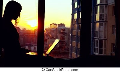 Silhouette of beautiful young brunette business woman working on her laptop during sunset. Girl sitting on the window at amazing modern building blurred background in city