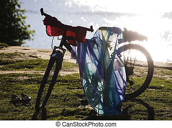 silhouette of bicycle leaved on coast with clothes