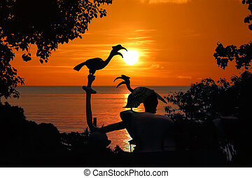 Silhouette of Birds Hornbill statue with trees and red sky sunset