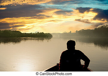 silhouette of boatsman rowing out into the yamuna ganga river in the morning