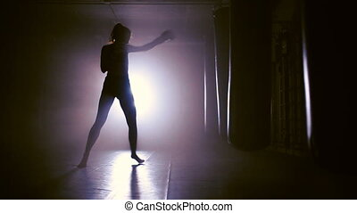silhouette of Boxing training in smoke - Woman Punches In...
