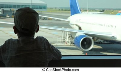 Silhouette of boy close up looks through window at planes at airport
