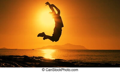 silhouette of boy jumping at sunrise on beach - silhouette...