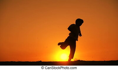 silhouette of boy jumping at sunset