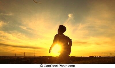 Silhouette of boy launching his airplane against sunset -...