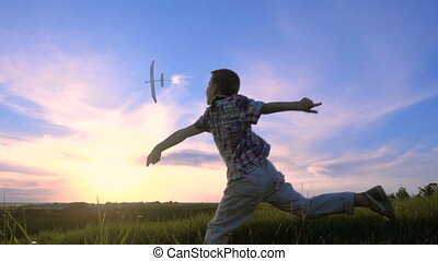 Silhouette of boy launching his airplane against sunset,...