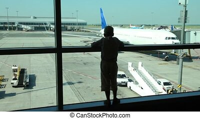 Silhouette of boy looks through window at planes at airport