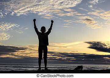 Silhouette of boy raising arms by ocean.