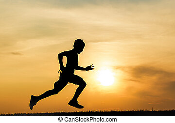Silhouette of boy running at sunset.