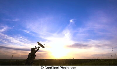 Silhouette of boy running with airplane against sunset