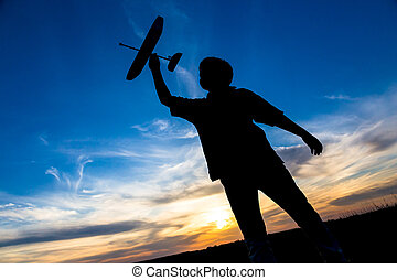 Silhouette of boy with his airplane against sunset