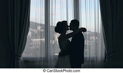 Silhouette of bride and groom who kissing near the window
