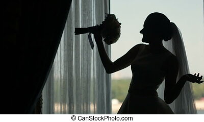 Silhouette of bride besides the window with her wedding bouquet