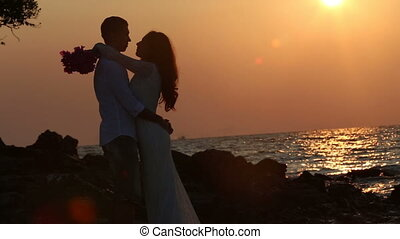 silhouette of bride hugs and kisses groom