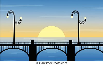 Silhouette of bridge with street lamp at sunset scenery