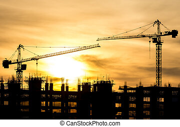Silhouette of building and crane