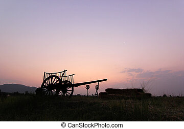 silhouette of bullock cart in field with sunrise background