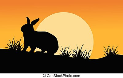 Silhouette of bunny and grass at sunset