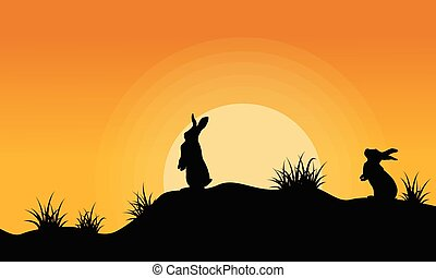 Silhouette of bunny on the hill at sunset