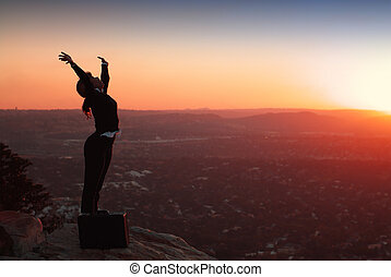 Silhouette of African American Business Woman ontop of Hill during Sunset