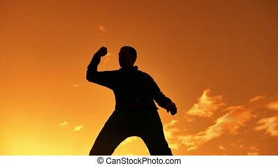 Silhouette of Businessman Celebrating Success Happiness on a mountain top Sunset Evening Sky Background, Sport lifestyle and active life Concept. Business man sunset sunlight