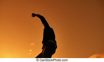 Silhouette of Businessman Celebrating Success Happiness on a mountain top Sunset Evening Sky Background, Sport and active life Concept. Business man sunset sunlight lifestyle
