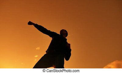 Silhouette of Businessman Celebrating Success Happiness on a mountain top Sunset Evening Sky Background, Sport and active life Concept. Business man lifestyle sunset sunlight