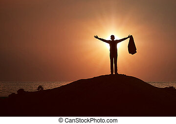 Silhouette of businessman raised hands and praying to god