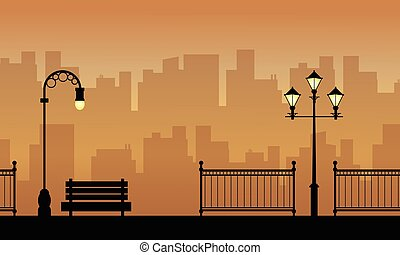 Silhouette of chair fence and lamp on street