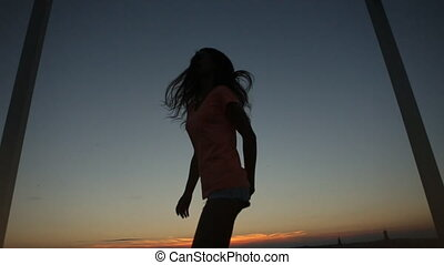 Silhouette of charming girl jumping and turning on the city bridge and raising her hands up. Sunset background