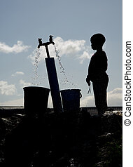 Silhouette of a young boy gathering water at a well in Langa, South Africa, a township located on the outskirts of Cape Town.