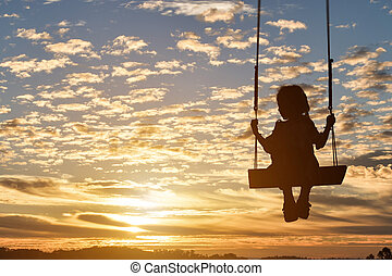 Silhouette of child girl is swing in sunset