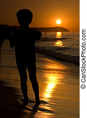 Silhouette of child on sand beach during sunset