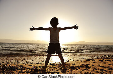Silhouette of child on the beach, holding his hands up, ...