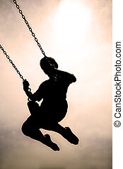 Silhouette of Child Swinging on PLaygroung Swingset - A...