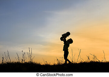 silhouette of child with bear on sunset