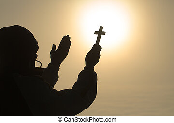 Silhouette of christian Man holding a cross cross in hands praying for blessing from god on sunlight background, hope concept