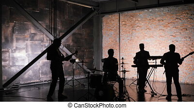 silhouette of Concert rock band performing on stage with...