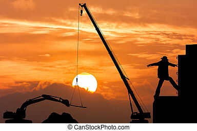 silhouette of construction foreman worker controlling the excavator and crane